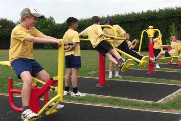 Trẻ em thích thú với máy tập thể dục ngoài trời